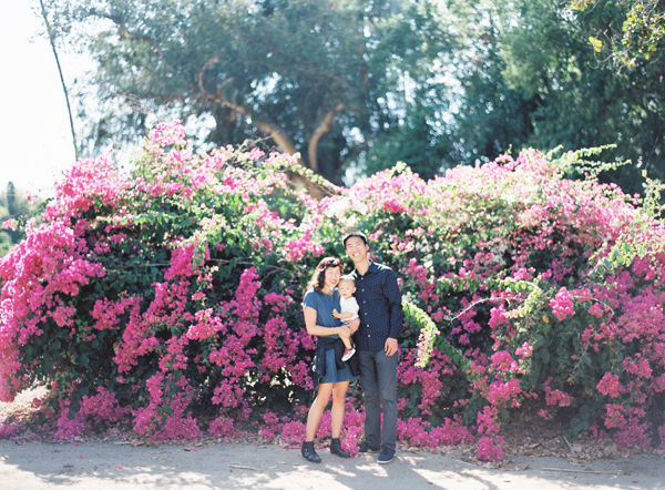 family picture in front of flower bush by The Great Romance Photo