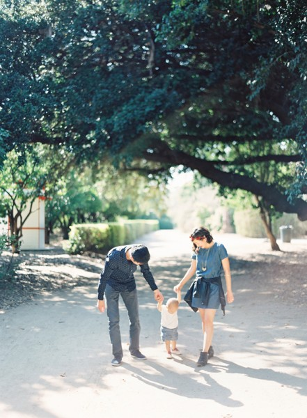 mom and dad walking with toddler by The Great Romance Photo
