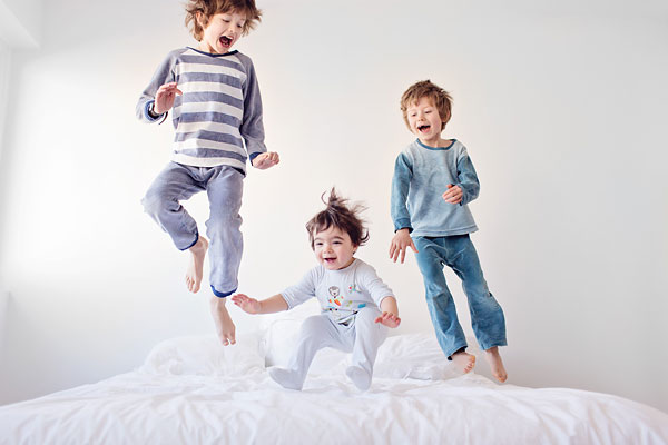 natural light photo of kids jumping on bed by French photographer Lisa Tichane of Tout Petit Pixel