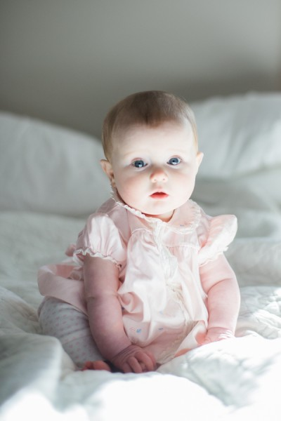 photo of baby sitting on bed by rodeo and co photo