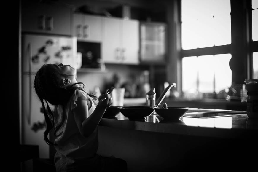 black and white photo of girl in kitchen by Niki Boon