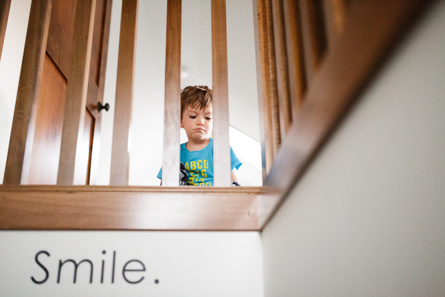 boy pouting on stair balcony photograph by Erica Caligiuri