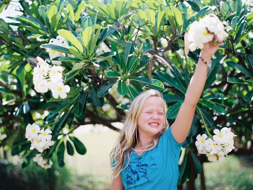 maui photographer wendy laurel's image of joyful girl in plumeria tree