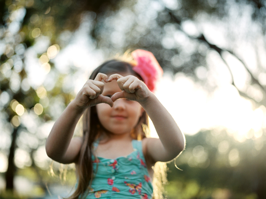 backlit photo of little girl making a heart with fingers by cassi green