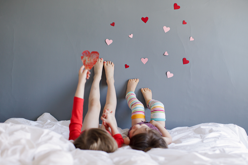 crystal hardin's image of these two sisters feet on wall with hearts