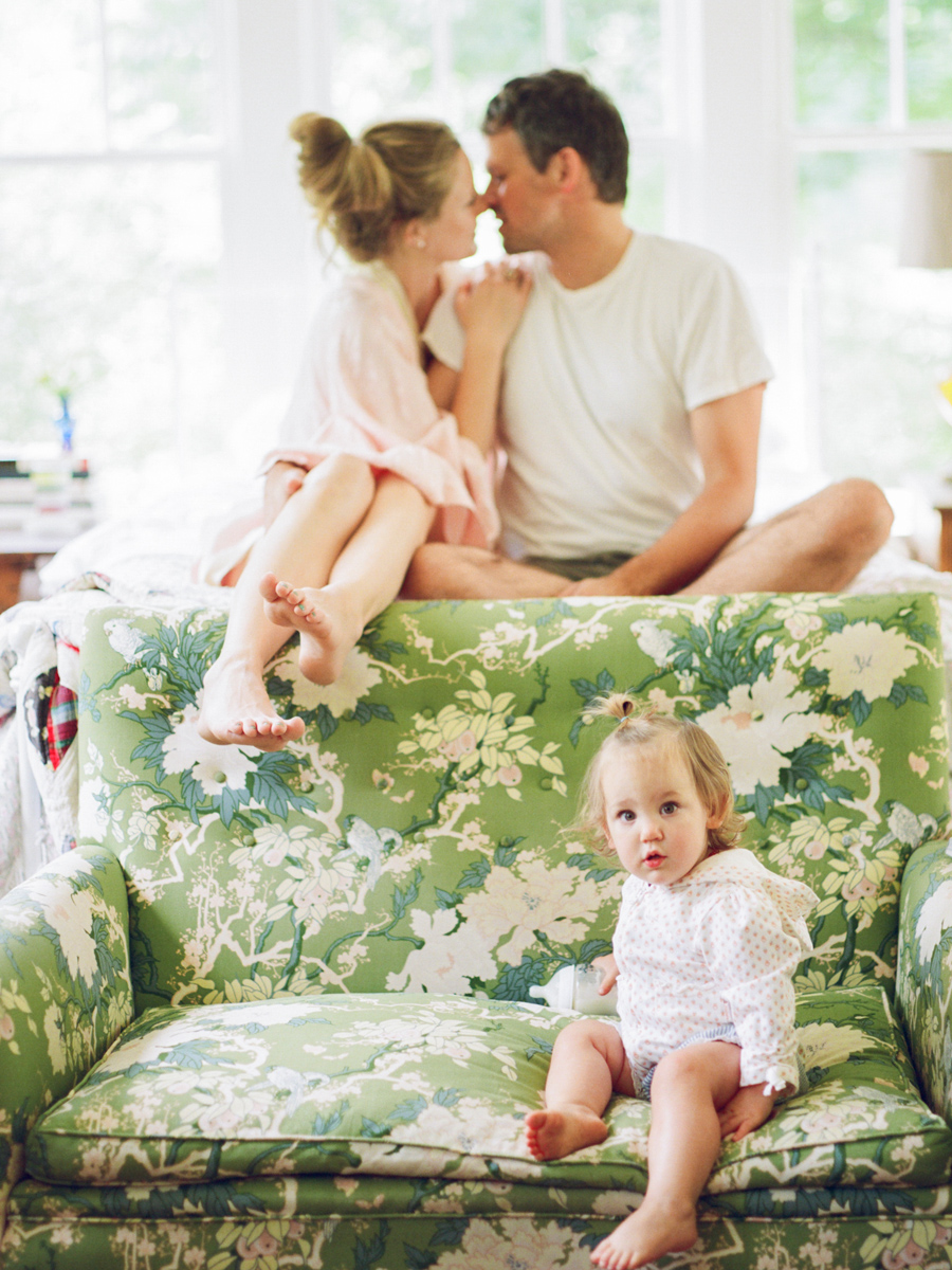 photographer beth morgan's film image of girl on green couch with parents kissing