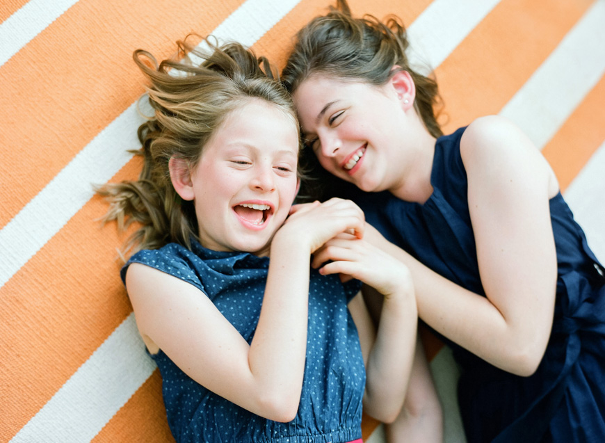 Gorete_Ferreira_Photography's image of two sisters laughing on striped rug