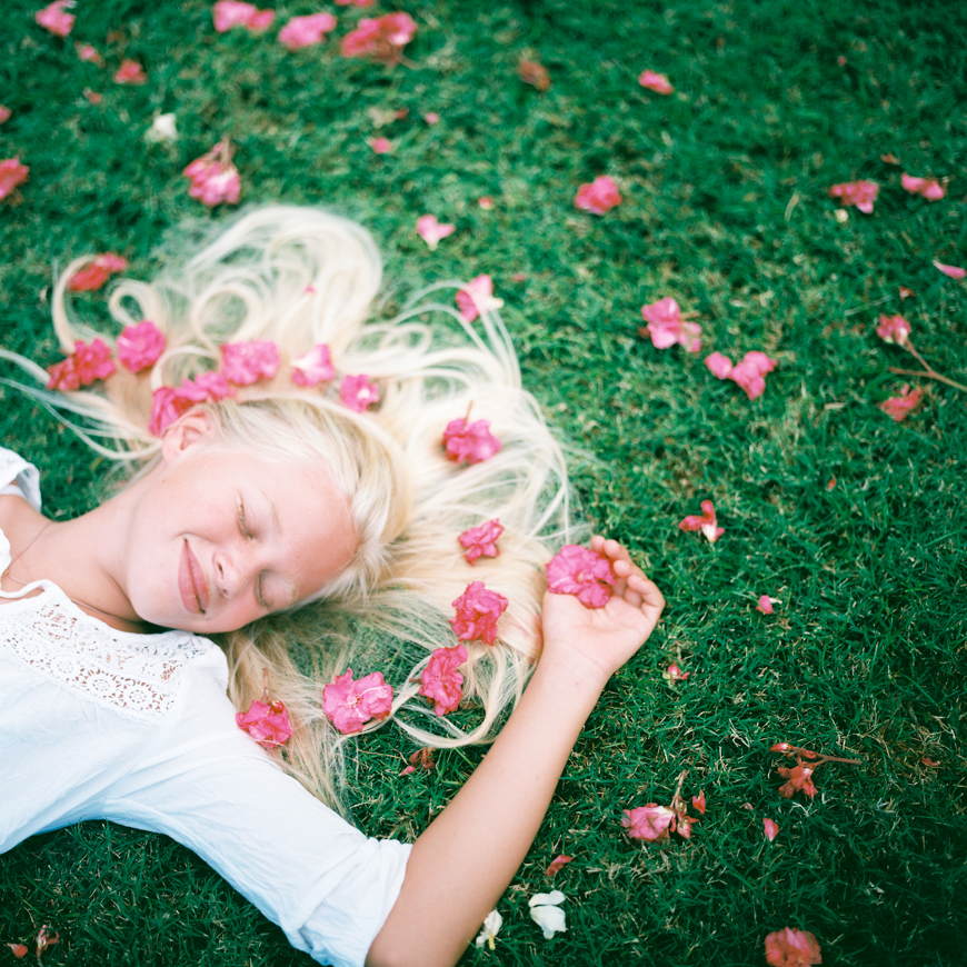 photo of girl laying in grass with pink flowers by maui photographer wendy laurel