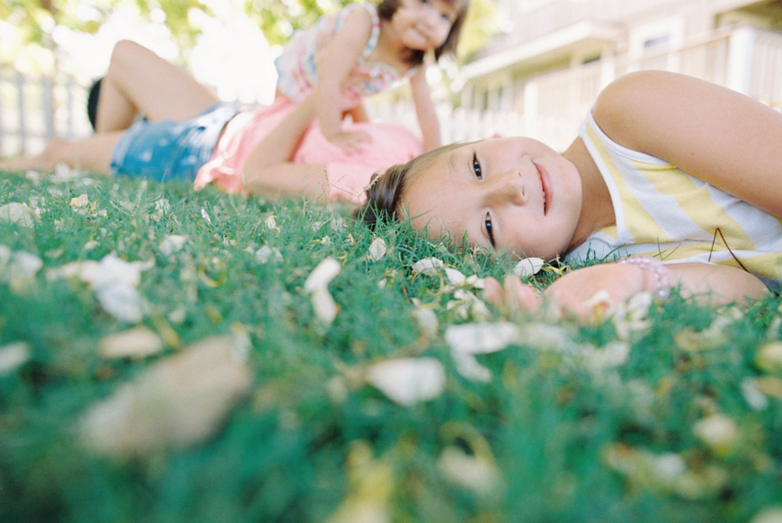 maui photographer wendy laurel's photo of girl in green grass with sister laughing behind