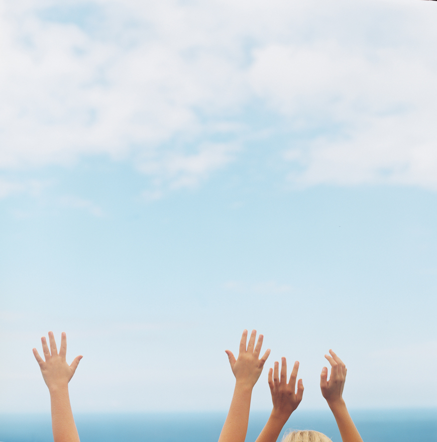 photographer wendy laurel's image of girls with hands in air with blue sky