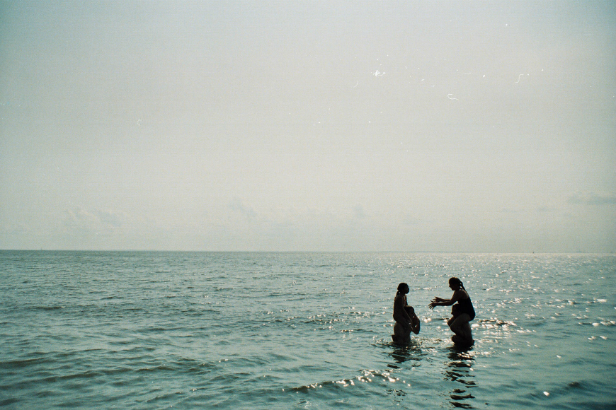 photographer jennifer trovato's image of girls playing in ocean negative space