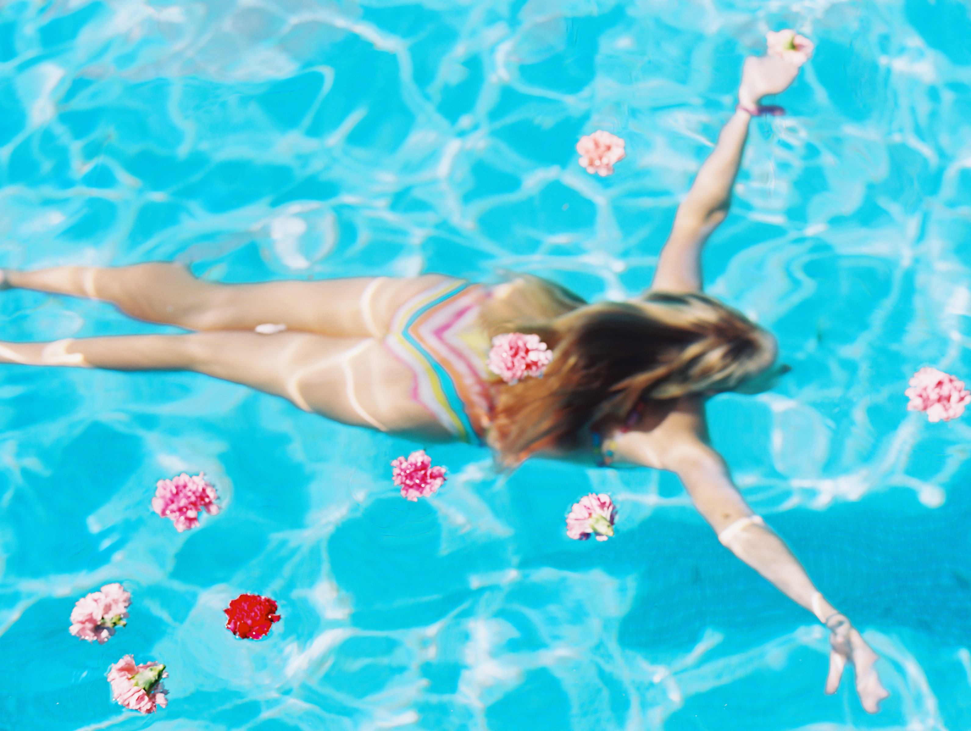 maui photographer wendy laurel's image of girl in rainbow suit in pool with flowers