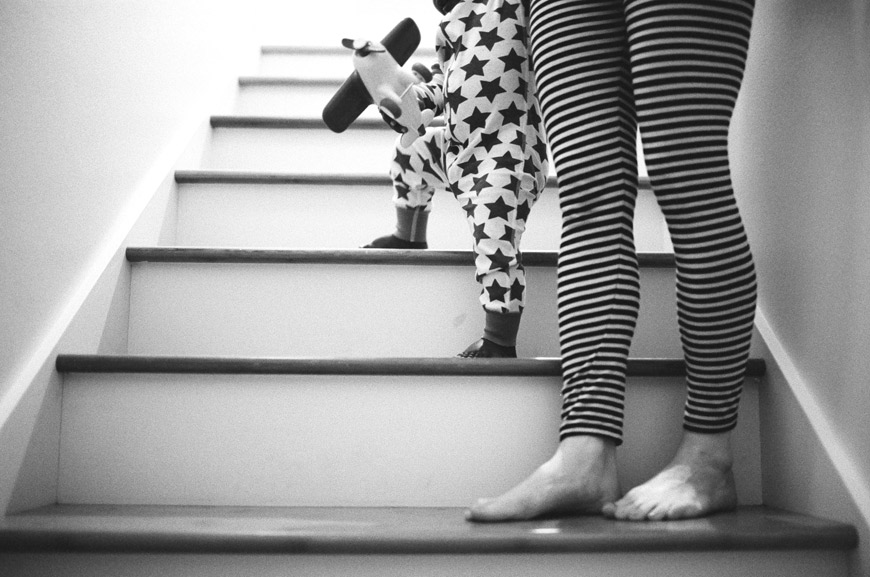 amazing black and white photo of mom and son in striped pjs on stairs by photographer caterine abegg