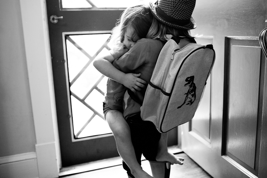 black and white image of two sisters hugging in front of door by photographer crystal hardin (1 of 1)