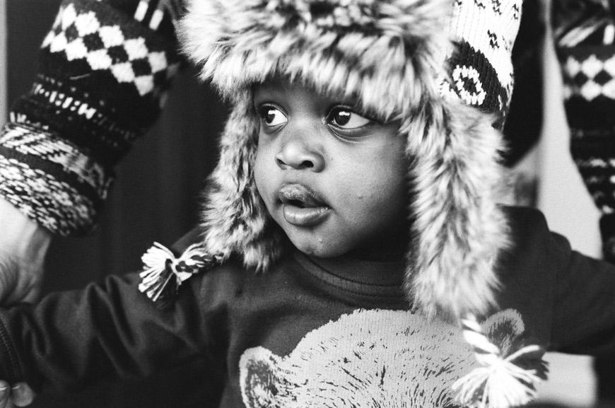 black and white protrait in child in winter hat by photographer Catherine Abeg