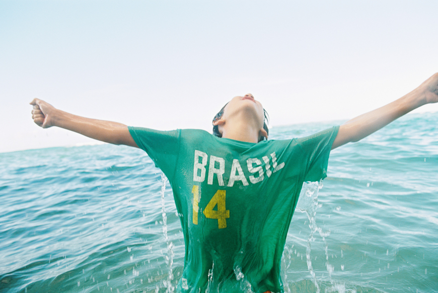 boy in brasil shirt in water jumping for joy by photographer wendy laurel