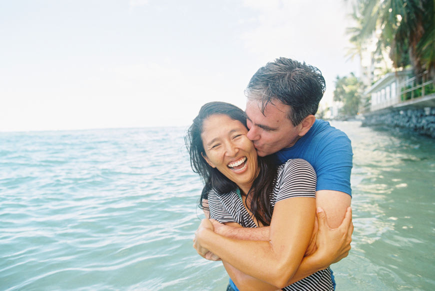 laughing hug photograph of husband and wife in ocean by maui photographer wendy laurel