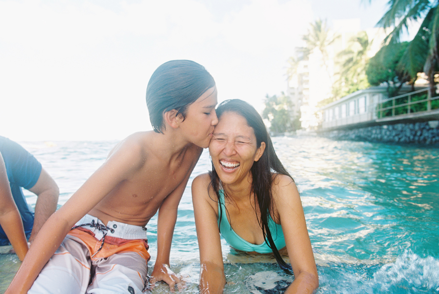 boy kissing mom in ocean near waikiki by wendy laurel