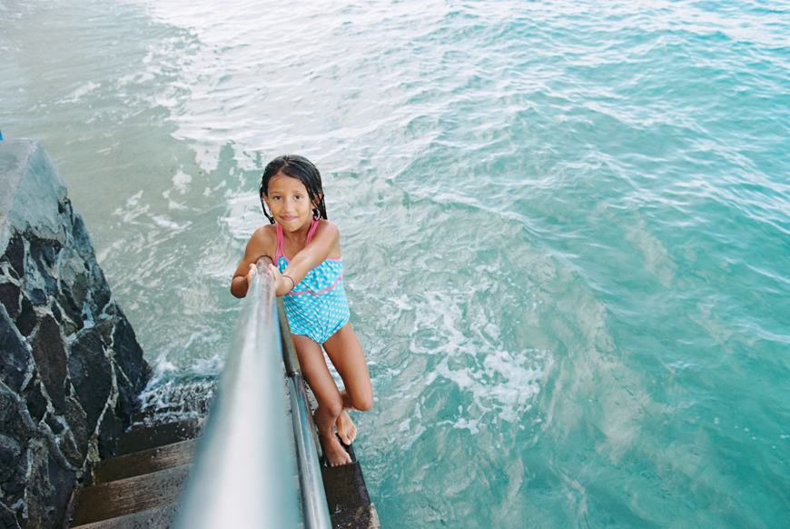 photograph of girl on railing in ocean by photographer wendy laurel