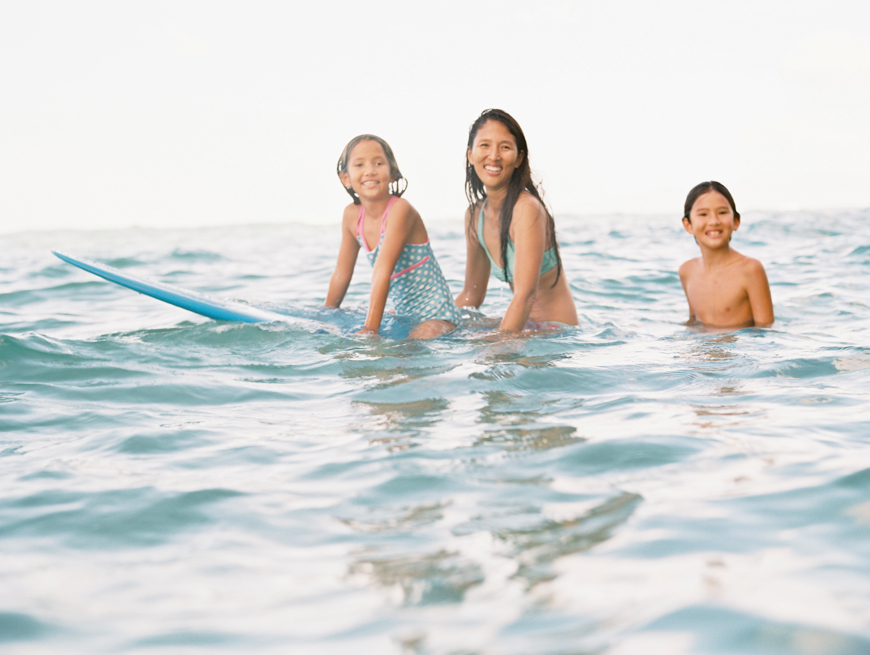 ocean portrait of mom and kids on surfboard in waikiki by photographer wendy laurel