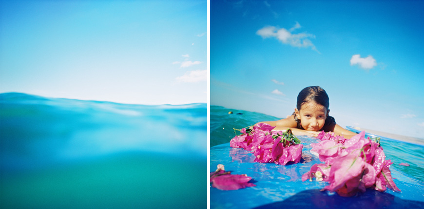 girl in water with pink flowers in ocean by photographer wendy laurel