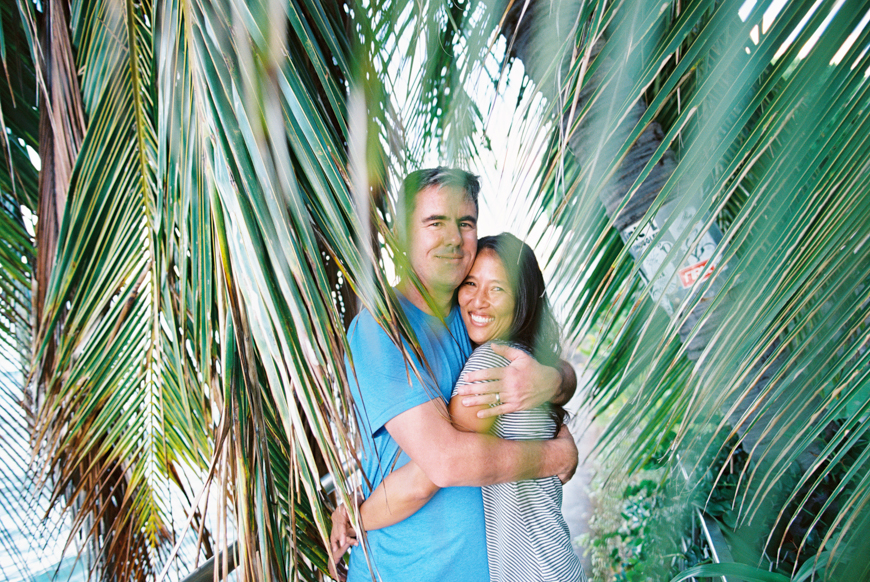 hawaii photographer wendy laurel's portriat of couple under palm fronds with film