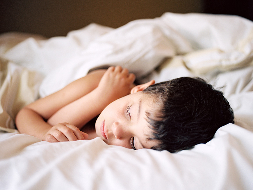 hannah mayo's image of son sleeping in white sheets