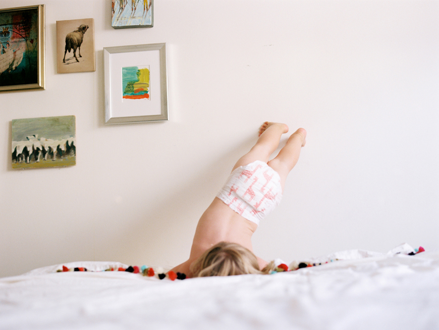 kauai photographer rachel thurston's portrait of kid with feet on wall
