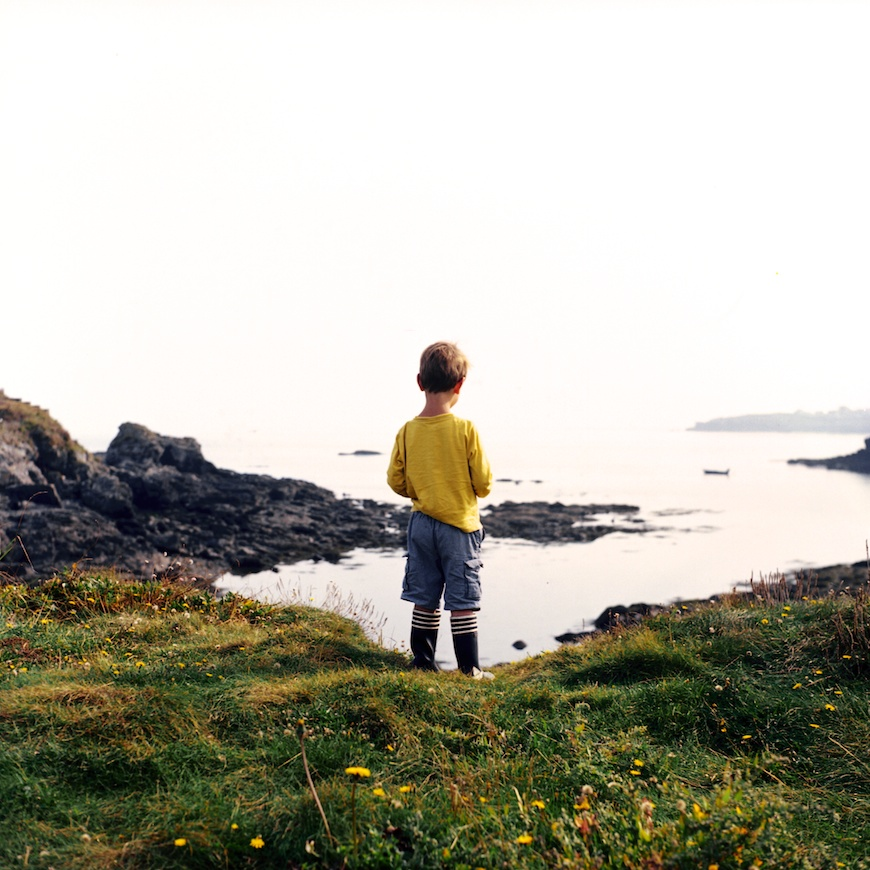 boy in yellow shirt and striped boots on green hill next to coast photo by lea jones
