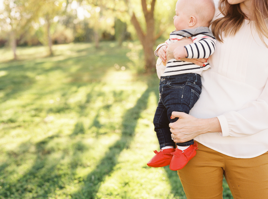 bright and sunny natural light photograph of mom holding baby in striped shirt and red shoes by photographer samantha kelly