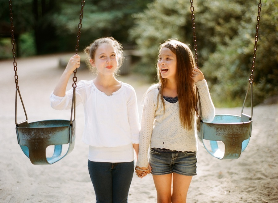 film photograph of two girls next to swings by photographer amy grace of a beautiful life photo
