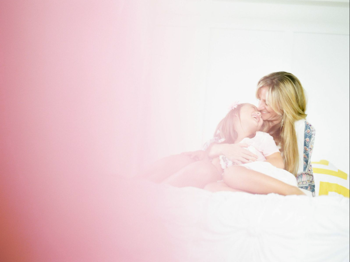 gorgeous and creative image by yan photo of mom and daughter on bed shot through pink haze