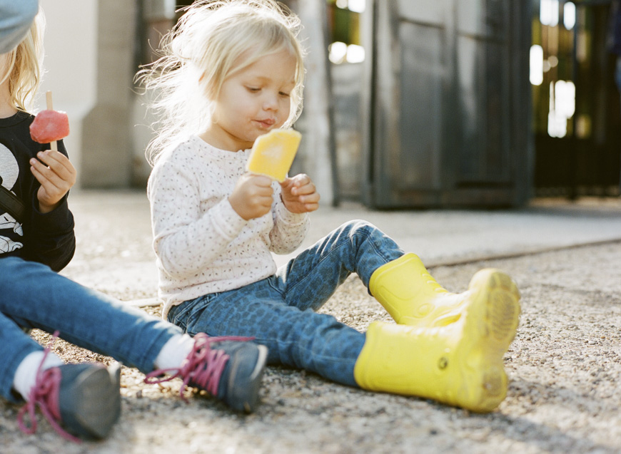 gorgeous backlit portrait of young blonde girl with yellow boots eating orange popsicle by photographer misty perryman