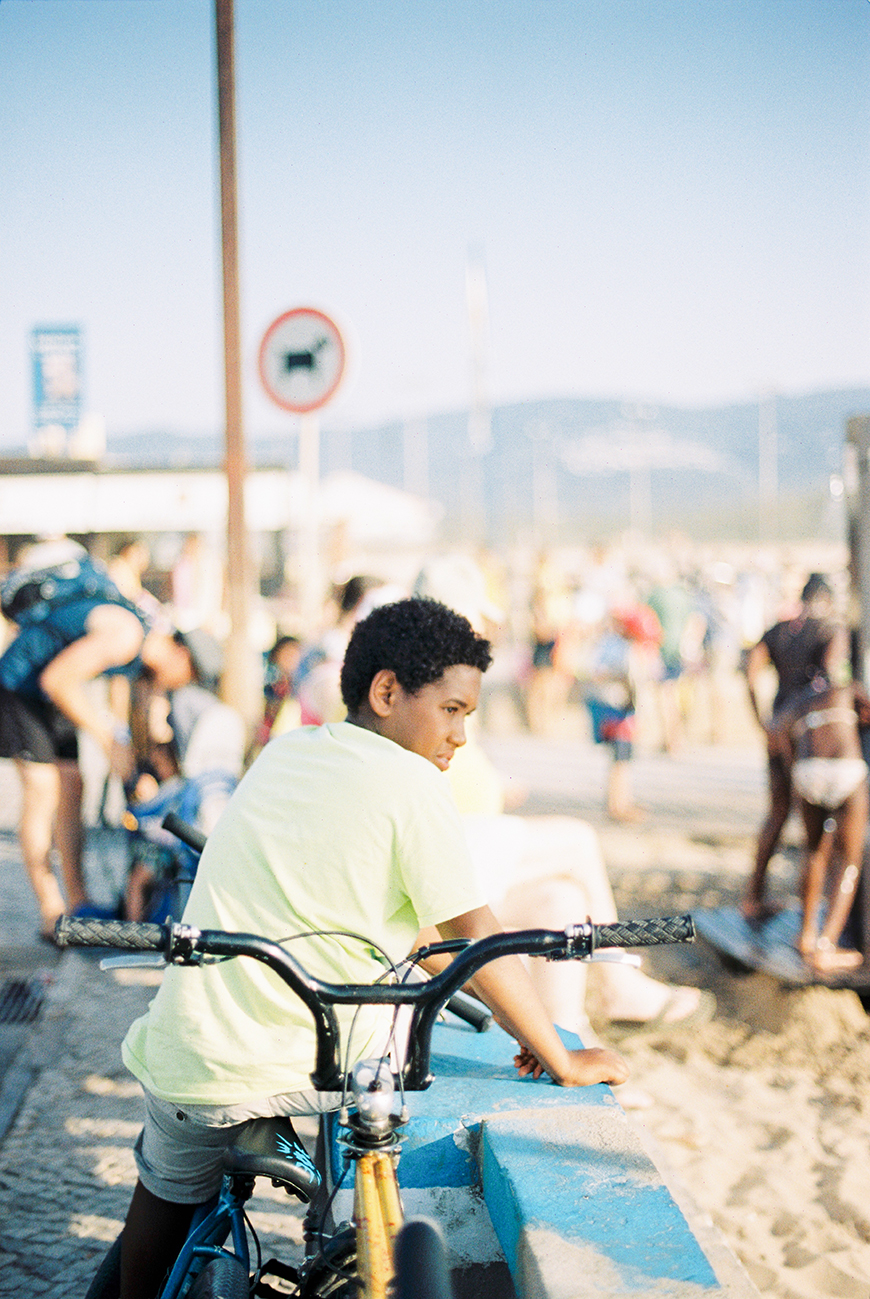 image of boy on bike at blue wall next to beach by photographer susana gomes