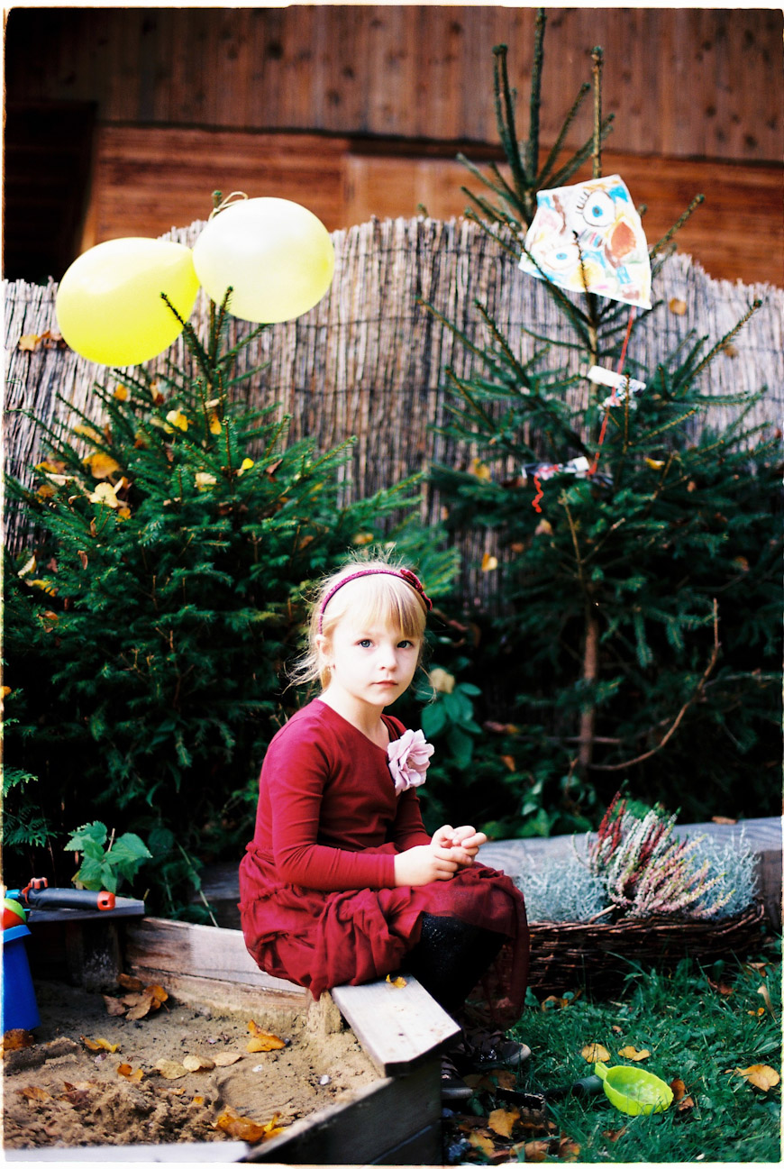 katarina tubio's photograph of girl in red dress with pine trees and balloon