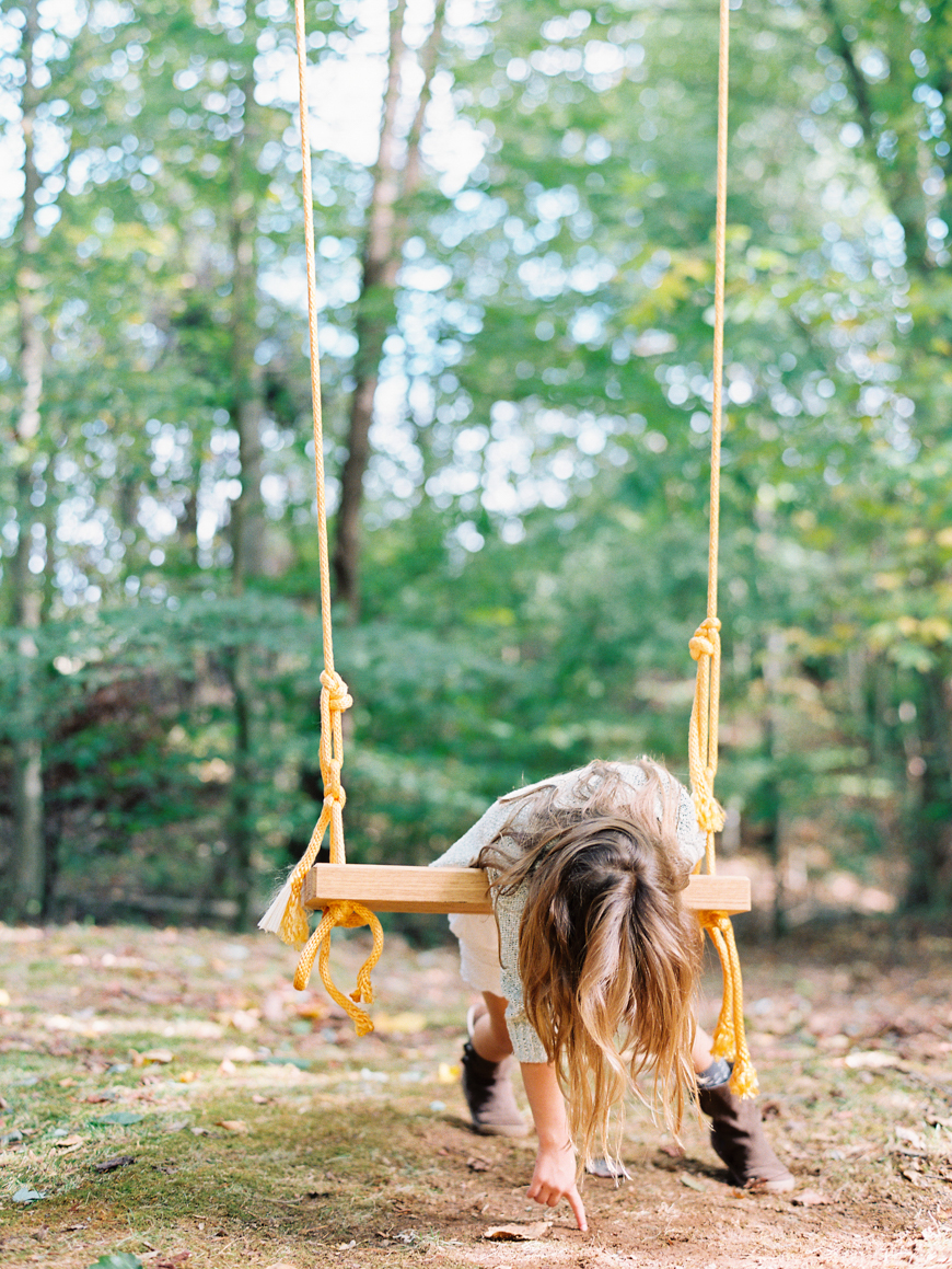 mara wolff's photograph of girl on swing with yellow ropes against green trees
