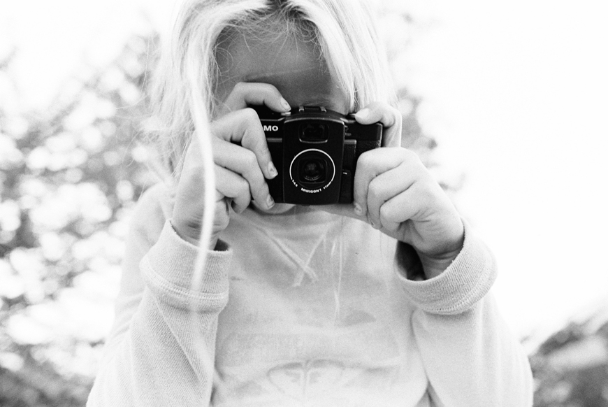 maui photographer wendy laurel's photograph of girl in black and white shooting a lomo camera