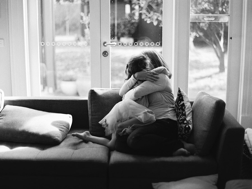 mom and daughter hug on couch image by photographer sarah black