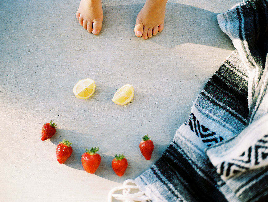 nikki martinez's photograph of kids feet with happy face of lemons and strawberries
