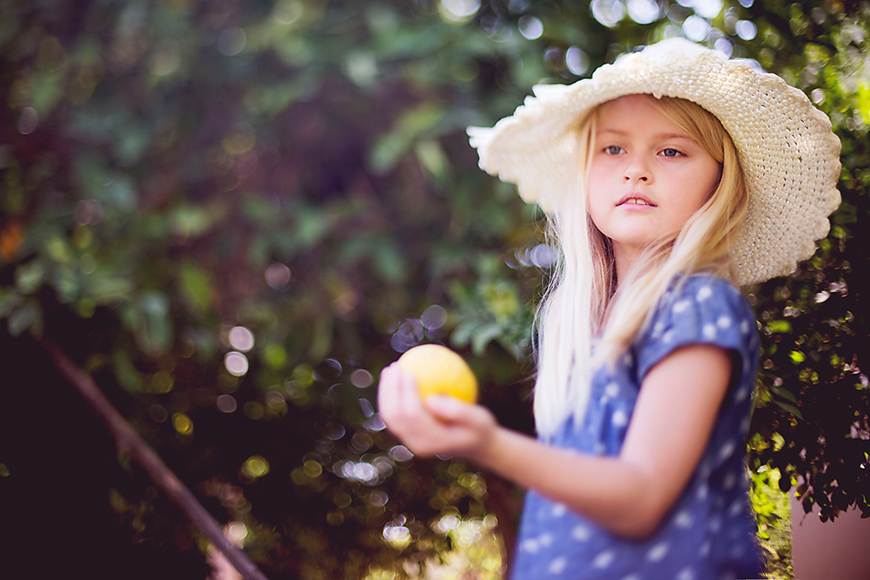 photographer erin hensley's photo of natural light portrait of girl in straw hat with lemon free lensed