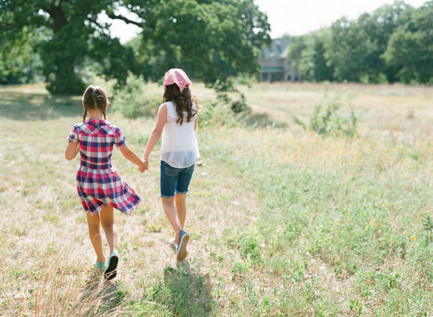 photographer jenny mccann's image of girls walking in field holding hands