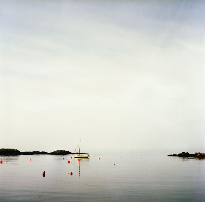 photographer lea jones's image of water with sail boat and red buoys