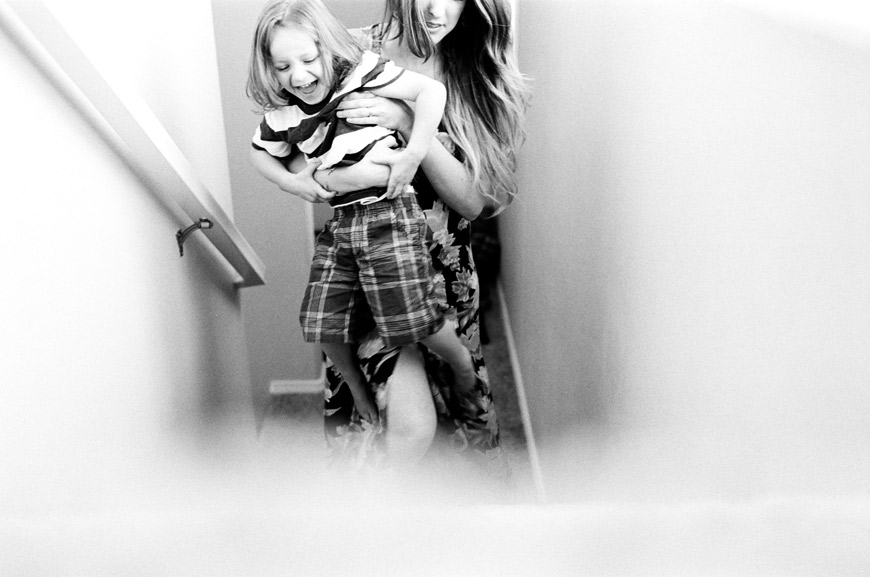 rad creative black and white photo of mom and son on stairs by photographer catherin abegg