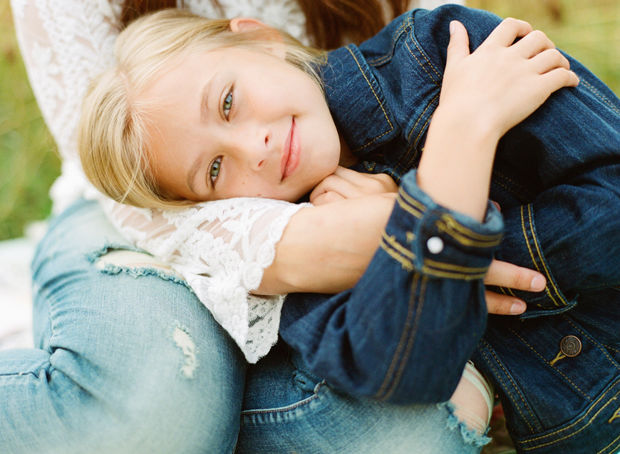 simply splendid's image of daughter in jean jacket with head in moms lap on film