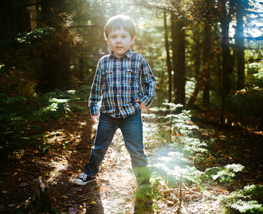 stunning lifestyle portrait of son in flannel shirt in sun fllled woods.jpg
