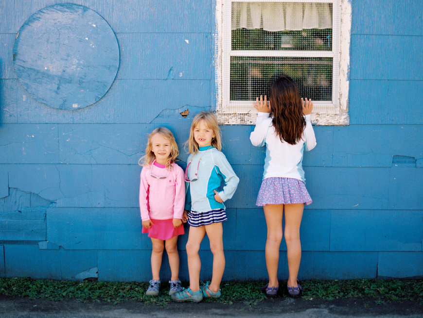 cute little girls against a blue wall film image by photographer erin hughes