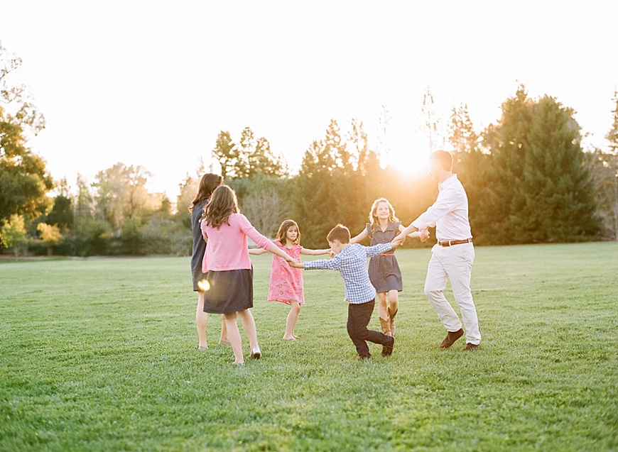 gorete ferreira photography's natural light image of family playing ring around the rosie in golden light
