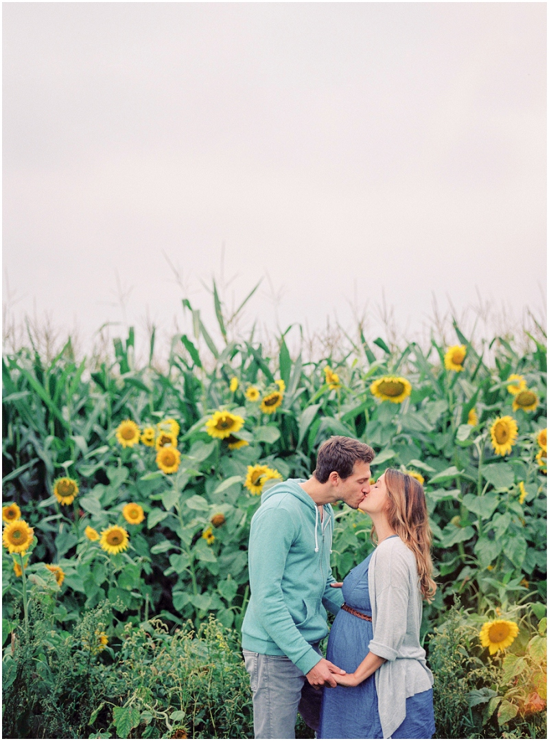 gorgeous film image of couple kissing in sunflower field with negative space