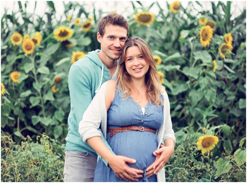 gorgeous film image of maternity girl with husband in sunflower field