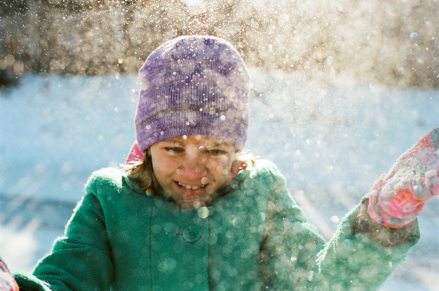 gorgeous natural light photo of girl in purple hat in snow by photographer natalie seeboth